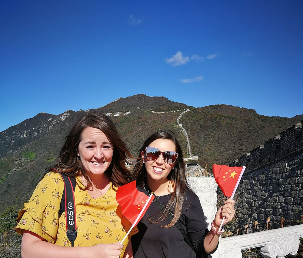 China Visa Layover. Standing on the Great Wall of China holding Chinese flags during our 24 hour layover in Beijing.